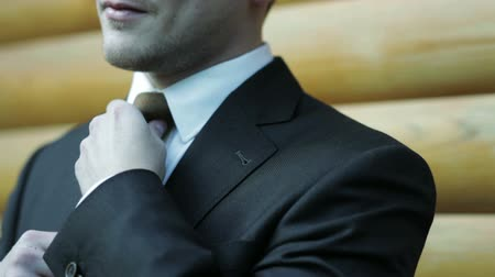 bogaty : Man adjusts necktie close-up