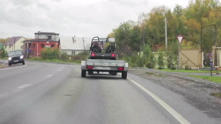 farm equipment : Car with a trailer traveling on the road Stock Footage
