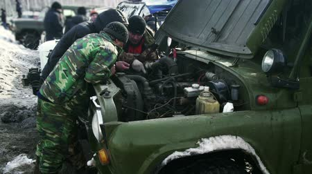 maska : Three men trying to repair the car in a forest Wideo
