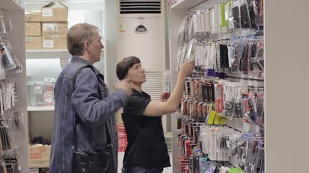 elektronika : Seller helps the buyer to choose the goods in the shop of accessories Wideo