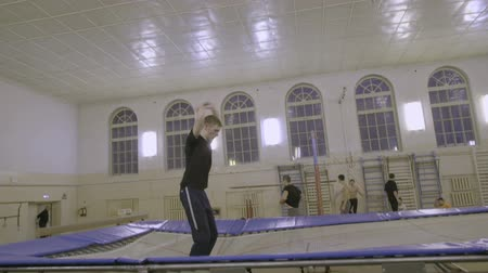 отскок : Man jumping on the trampoline in the sports class Стоковые видеозаписи