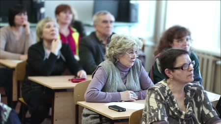 лекция : Aged people listen to a lecture sitting in a classroom
