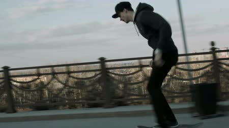 patim : Guy rides a skateboard on the sidewalk of the road bridge Vídeos