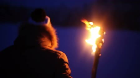 meşale : A young guy with the torch goes through the snow-covered field at night Stok Video