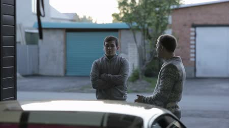 осмотр : Two men discussing something near the repair shop Стоковые видеозаписи