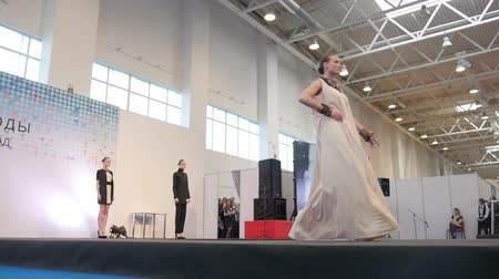 pist : Fashion show. Female models in dresses go on the catwalk in slow motion Stok Video