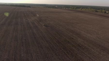 Aerial view flying over the top of a combine harvester and tractor in a field