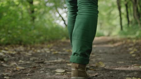 The legs of a young girl who goes away, green jeans and sneakers Stock Footage