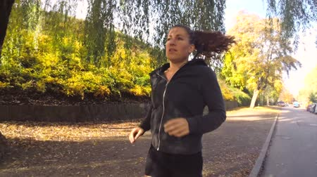 atleta : Young active female athlete exercising outdoor in the sunny autumn. Running close to a park. Healthy women.