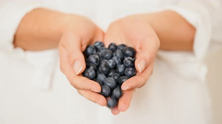 Handful of blueberries getting poured down from female hands. Caucasian woman holding blueberries in her cupped hands.