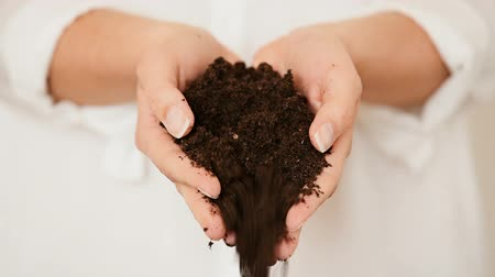 talaj : Caucasian female model pouring black soil from the palm of her hands.