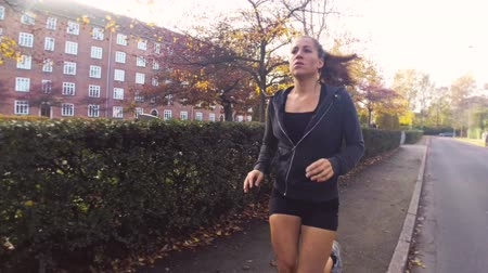 sport : Slowmotion footage of a fresh fitness woman running near a park in the autumn. The model is in the 20s and wearing sportswear.