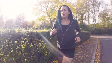 Slowmotion footage of a young fitness woman running in the autumn. The model is in the 20s and wearing a cardigan with hood.  Stock Footage