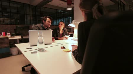 négy ember : Four young people sitting around a table making a new business plan. Creative people discussing work during a meeting in a modern office. Stock mozgókép