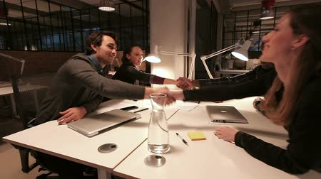 tratar : Young executives shaking hands and leaving a meeting. Closing a successful deal.
