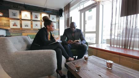 Young african people sitting at cafe researching information on internet. Business people at cafeteria with man holding digital tablet and woman writing notes. Stock Footage