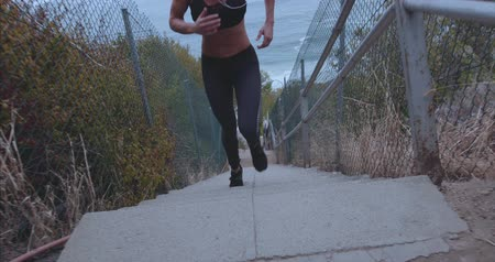 atlet : Outdoor shot of fit young woman running up stairs. Female athlete climbing up the steps.