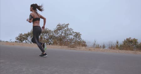 atlet : Outdoor shot of fitness woman running on open country road in morning. Female athlete on outdoor training session.