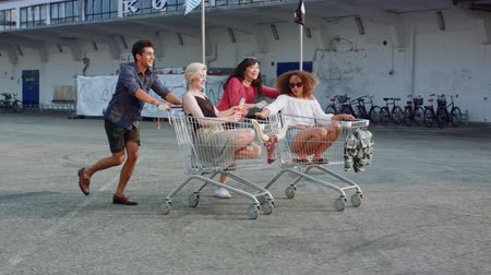 amalucado : Young friends racing grocery carts. Multiracial group of young people enjoying outdoors with shopping trolley race. Stock Footage