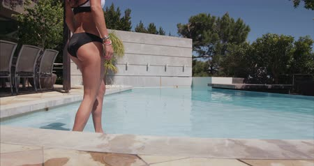 bra : Beautiful young woman walking out of the pool. Healthy female model in swimwear stepping out of the swimming pool. Wideo