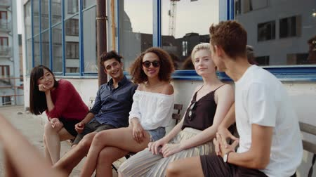chatting : Group of young people sitting at cafe and talking. Five young friends hanging out at outdoor coffeeshop. Stock Footage