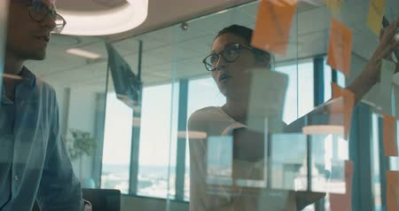 Business woman presenting her ideas to male colleague on sticky notes over glass wall. Business man and woman brainstorming in modern office. Stock Footage