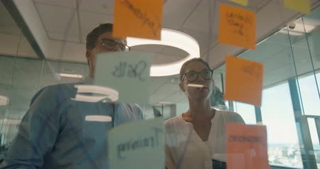 pont : Business colleagues having a discussion over sticky notes on glass wall. Business colleagues meeting in front of glass wall with adhesive notes.