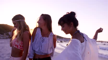 strand : Slow motion video of female friends dancing at the beach in evening. Group of young women having fun on the sea shore on a summer day.