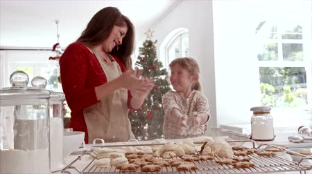 keksz : Smiling mother and daughter playing with cookie flour at kitchen counter while making Christmas cookies. Baked cookies and muffins on tray for Christmas. Stock mozgókép