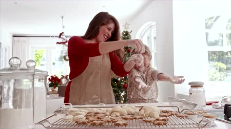 Smiling mother and daughter playing with cookie flour at kitchen counter while making Christmas cookies. Baked cookies and muffins on tray for Christmas eve.