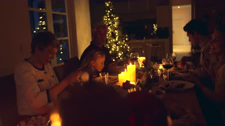 família : Christmas eve dinner, family sitting at dining table enjoying dinner together. Family celebrating christmas together at home. Vídeos