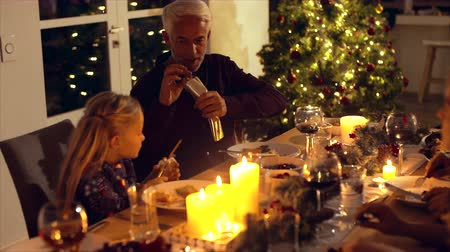 família : Little girl giving Christmas gift to her grandfather sitting at dinner table. Family exchanging presents during thanksgiving dinner at home. Vídeos