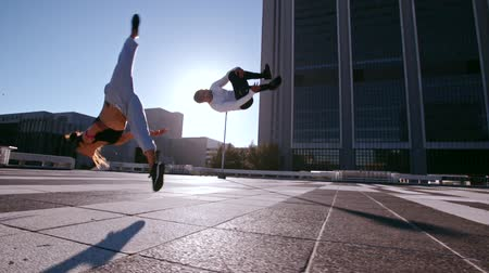 akció : Young man and woman practicing parkour in the city. Urban runners in action doing flips outdoors.