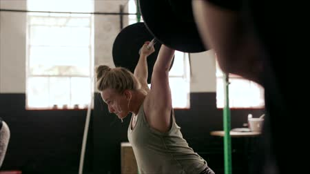 Strong woman lifting heavy weights in cross fit gym. Female athlete with muscular body lifting weights at health club.