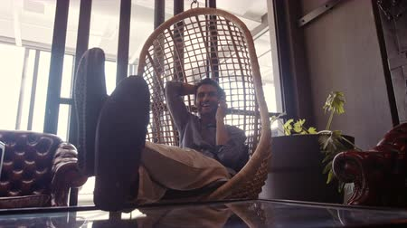 Young man sitting on a wicker hanging chair in office lounge and talking on mobile phone. Business man relaxing in office lounge during break. Stok Video
