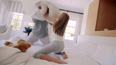 almofada : Young woman and her little girl playing with cushions on bed. Mother and daughter having a funny pillow fight.