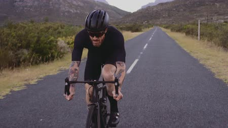 Tracking shot of a professional athlete cycling on long flat highway road in countryside. Strong man riding bike on countryside empty flat road.