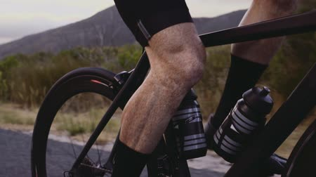 Close up on legs of road cyclist riding bicycle outdoors. Fit male cyclist cycling hard outdoors, focus on muscular legs pedalling bicycle.