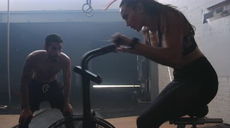 Fit young woman exercising on air bike in gym encouraged by friends. Female training on air bike with friends. Stok Video
