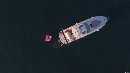 matrace : Aerial shot of friends jumping in the ocean from yacht and getting on a inflatable mattress. Young people enjoying a summer day sailing and swimming in sea water. Dostupné videozáznamy