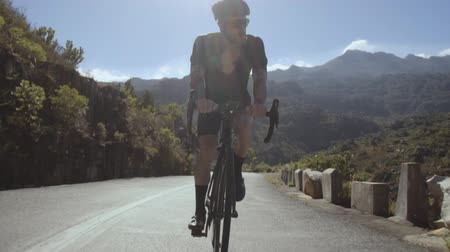 Tracking video shot of a male cyclist climbing up a mountain road. Man doing cycling training on a hilly highway road on a sunny day.