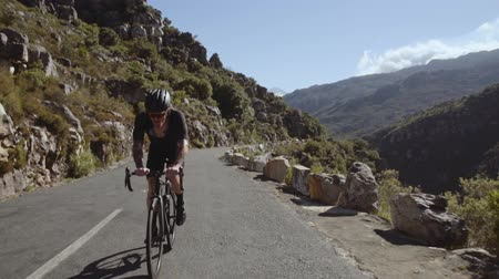Wide shot of a professional male cyclist riding his bike on a mountain road. Sportsman riding his bicycle on a mountain road.