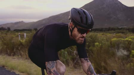 Close up video shot of fit sportsman wearing helmet and sunglasses cycling outdoors. Male cyclist riding bicycle outdoors on countryside road. Stock Footage