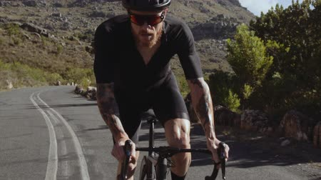 Slow motion video shot of a professional male cyclist doing uphill out of the saddle on road bike. Sportsman climbing up the hill on a bicycle. Stock Footage