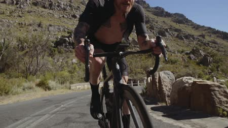 Fit  and healthy cyclist riding fast through mountain road. Man during intense bicycle ride training on a mountain road.