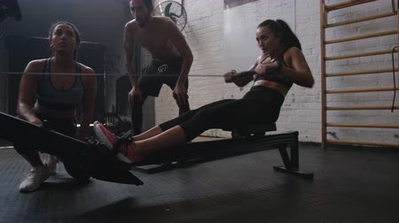 Sportswoman exercising on row machine in gym with trainers. Fit young woman exercising using rowing machine at health club.