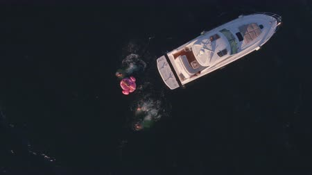 Aerial shot of friends diving in the sea from yacht and getting on a inflatable mattress. Group of friends enjoying a summer day sailing and swimming in ocean.
