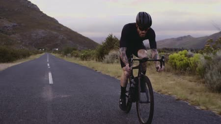 Wide angle shot of a male cyclist climbing up a mountain road. Man cycling on steep road on a hill.