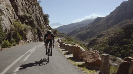 Tracking shot of a male cyclist doing uphill ride. Sportsman climbing up the curvy hilly road on a bicycle. Stok Video