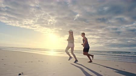 Fit young couple jogging together on the beach. Young man and woman running on the sea shore.